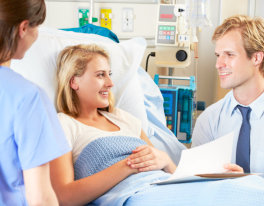 woman lying on bed talking to doctor