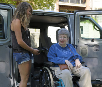 elderly woman on wheelchair and young woman standing